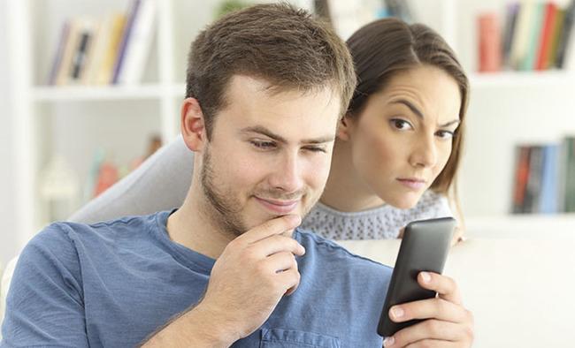 Девушка подсматривает, что парень делает в телефоне