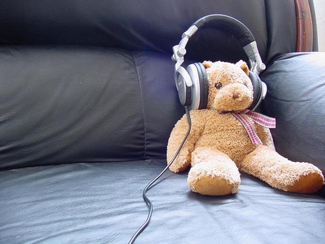 Игрушечный медвежонок в наушниках на диване