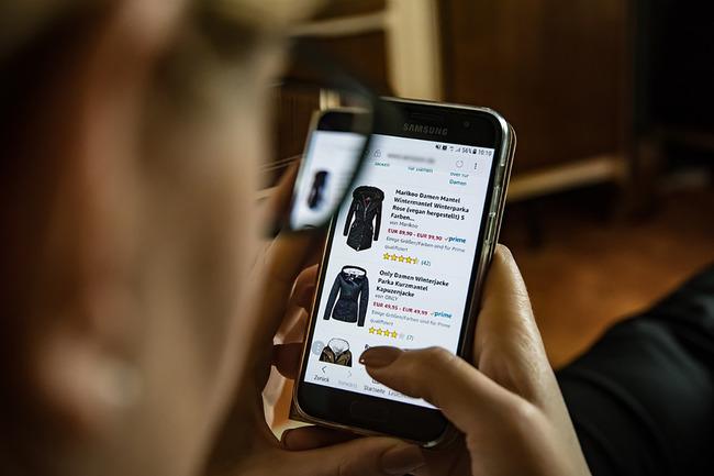 Человек в очках листает страницу онлайн-магазина