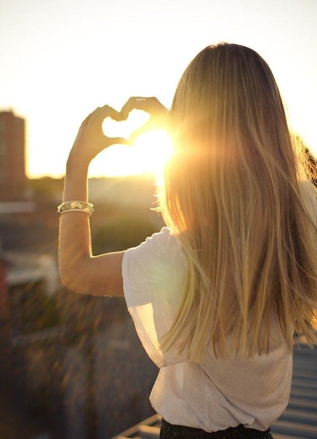 Девушка со спины делает сердечко пальцами