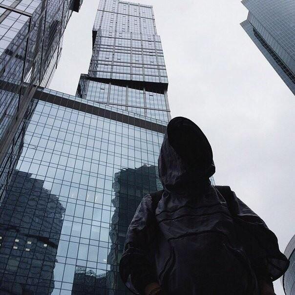 Человек в капюшоне на фоне небоскребов