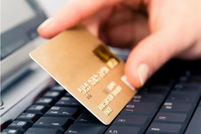 Пальцы держат банковскую карту напротив клавиатуры ноутбука