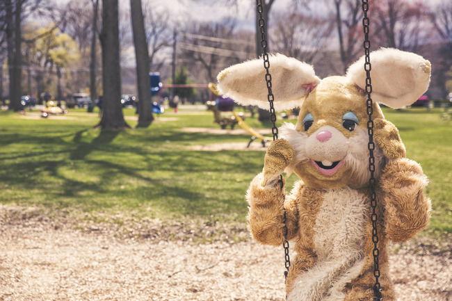 Человек в костюме кролика на качелях