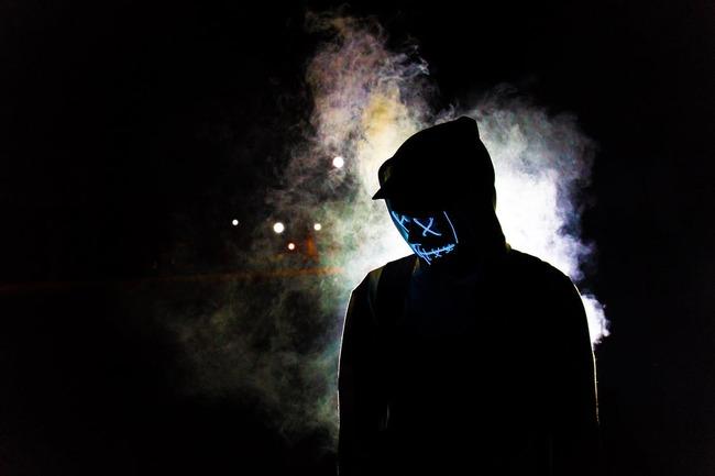 Человек с закрытым лицом на черном фоне