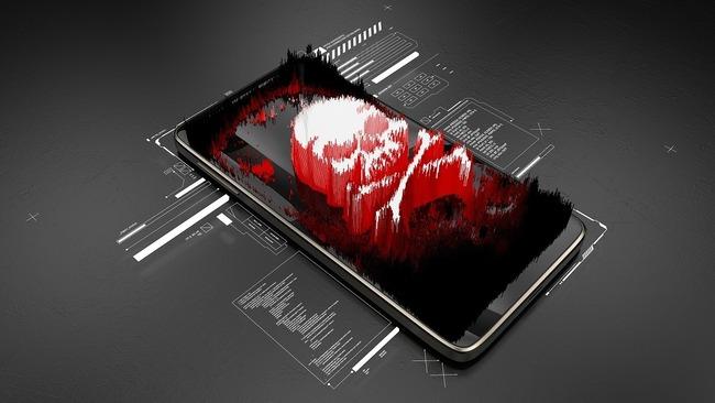 Красно-белый череп в лежащем на сером фоне мобильнике