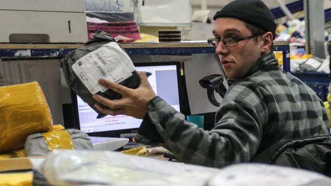 Оператор сидит в офисе и держит в руке пакет