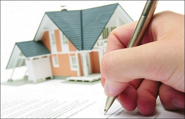 Рука с ручкой на фоне дома