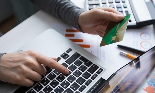 Ноутбук и банковская карта в руке