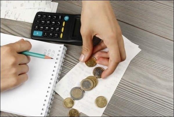 Рука с карандашом, калькулятор и монеты
